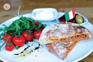 Ciabattabrot mit mediterranem Hackfleisch. Daneben ein Bündel Tomaten und ein paar Oliven in einer Schale.