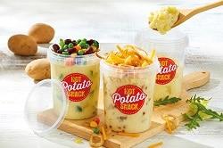 Stampfkartoffeln in drei großen Behältern für die Gastronomie mit Deko auf einem Holzbrett