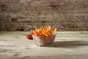 Süßkartoffel-Pommes von Farm Frites in einem Korb. Daneben eine Schüssel mit Ketchup.