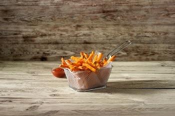 Süßkartoffelpommes von Farm Frites vor einem Holzhintergrund. Hinter den Pommes steht eine Schale Ketchup.