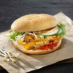 Ein belegter Veggie-Burger mit Saucen von Develey auf einem Stück braunem Papier