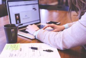 Eine Frau an einem Laptop, neben dem Laptop steht eine Kaffeetasse und liegt ein Blatt Papier mit Kugelschreiber