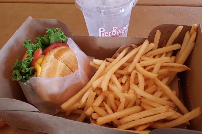 Ein Burger mit Pommes in einer to go Verpackung
