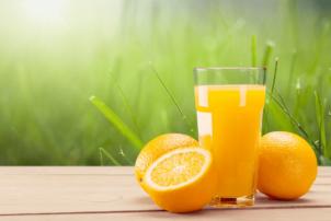 Ein frischer Orangensaft. Daneben Mehrere Orangen