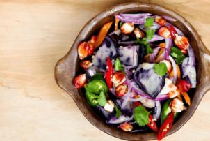 Eine vegetarische Bowl bestehend aus Zwiebeln, Paprika, Gurken und weiterem Gemüse