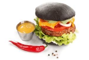 Ein Rezept für einen Black Burger Classic von Edna mit schwarzem Burger Brot, Bulette, Zwiebeln, Tomaten, Salat, Käse und einer Chilischote