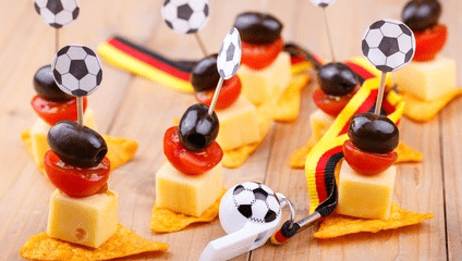 Kleine Snacks in Form von Käsestücken, mit Tomatenscheiben und Trauben auf einem Zahnstocher
