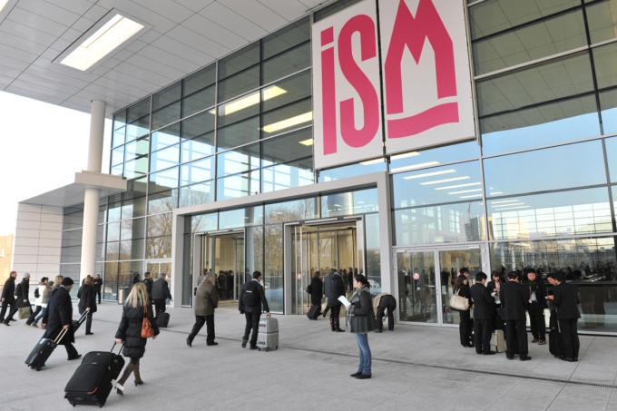 Der Eingang der Kälnmesse, wo die ISM stattfindet, ist auf dem Foto abgebildet. Über der Eingangstür hängt auf weißen Hintergrund in pinker Schrift der Schriftzug ISM. Die ISM ist die internationale Fachmesse für Süßwaren.