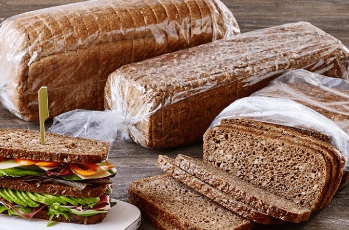Auf dem Bild erkennt man das abgepackte Brot in einem Brotschlauch von Kohberg. Links von den drei Brote, wovon zwei abgepackt und eins geöffnet ist, befindet sich ein Belegbeispiels mit Salat, Gemüse und weiterem Belag.