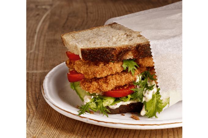 Ein Sandwich belegt mit Mini Schnitzeln von Salomon, Tomaten, Gurken, Salat und Remoulade