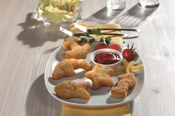 Meeresfiguren von MYCONFINO auf einem Teller angerichtet. Neben den Meeresfiguren sind Tomaten, Paprika und eine Schale mit Ketchup.