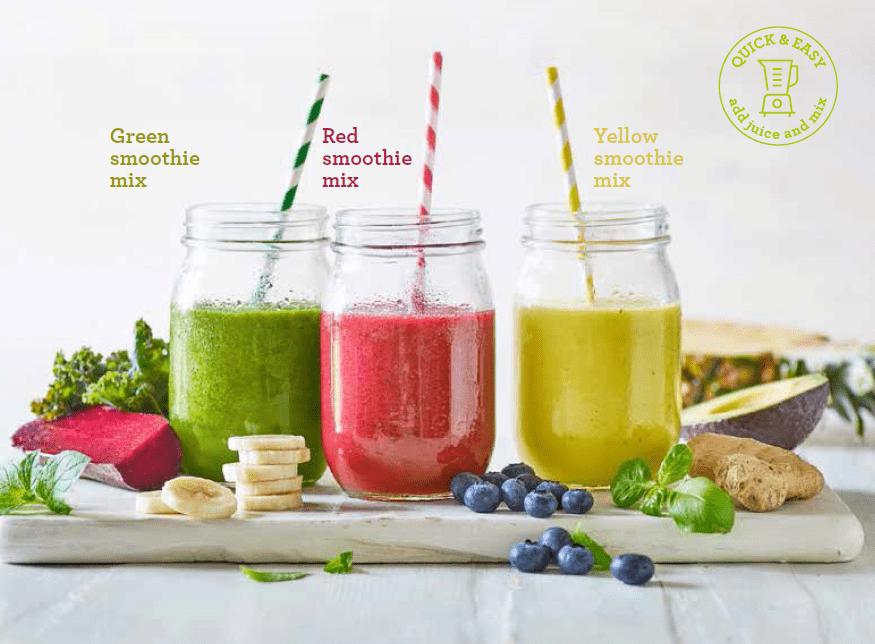 Drei unterschiedliche Smoothies von Ardo sind auf dem Bild in großen Gläsern zu sehen. Links ist der grüne Smoothie, in der Mitte der mit rpten Früchten und rechts der yellow Smoothie. In jedem Getränk befindet sich ebenfalls ein namensgleich-farbiger Strohhalm. Die Früchtegetränke stehen auf einem Schneidebrett auf einem hellen Holzfußboden. Um die runden Gläser herum sind Früchte, die in den jeweiligen Smoothies enthalten sind.