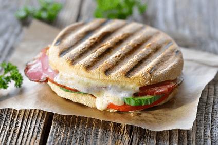 Auf dem Foto ist ein gegrilltes Brötchen zu sehen, welches mehrere Grillstreifen besitzt. Der Käse schmilzt zwischen den Scheiben, Außerdem ist es noch mit Tomate, Salami und Gurke belegt. Es liegt auf einem Grillpapier auf einem Holzboden.