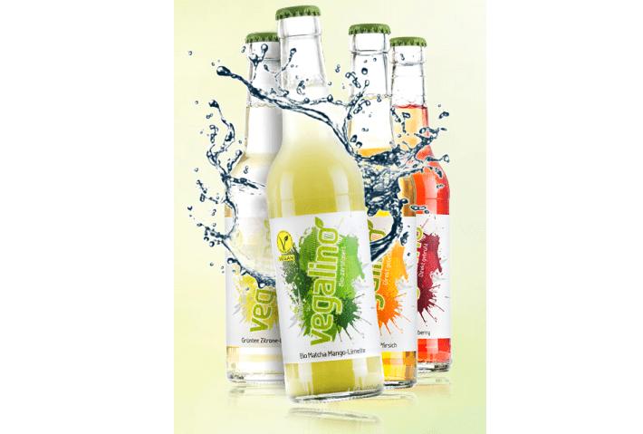 Mehrere Flaschen Vegalino sind in einem Dreieck hintereinander aufgestellt. Um die Teegetränke herum spritzt Wasser, welches benutzt wird um die Frische und Erfrischung des Produktes wiederzuspiegeln.
