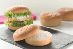 Ein Burger Brötchen aus Sauerteig ist in zwei Hälften geschnitten und liegt auf einem schwarzen Brett. Dahinter befinden sich noch weitere ungeschnittene Burger-Buns, aber auch ein Beispiel mit einem Sauerteig-Bun, der mit Salat, Patty und Soße belegt. wurde.