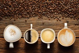 Vier verschiedene Variationen von Kaffee sind aus der Vogelperspektive zu sehen. Von links ist es ein Cappuccino, ein Americano, also Kaffee schwarz, ein Kaffee Crema und ein Milchkaffee. Die Kaffees stehen auf Holzboden und oberhalb des Bildes sind ganze Kaffeebohnen verstreut.