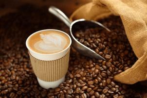 Ein Kaffee in einen Pappbecher steht zwischen vielen Kaffeebohnen, die gerade aus einem Sack Kafee raus fallen. Außerdem befindet sich neben dem Kaffeebecher eine silberne Schaufel für die Bohnen.