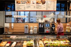 Auf dem Foto ist die Frontalansicht einer Auslage in einer Bäckerei zu sehen. Hinter der Auslage befindet sich eine Kaffeemaschine von Melitta. Außerdem stehen dort noch Teller neben und Tassen über der Maschine auf einem Regal. Ganz Oben hängt ein Schild mit allen Angeboten für die Kunden.