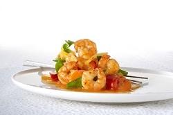 Scampis in süß-saurer Soße nach Chinesischer Art, angerichtet auf einem weißrn Teller mit Essstäbchen