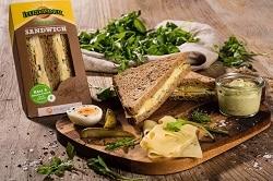 Auf dem Foto ist das Leerdammer Original Sandwich zu erkennen. Die Sorte mit der Rucolacreme ist abgebildet. Links befindet sich das doppelte Sandwich in einer dreieckigen Verpackung, die das Snacken leichter machen soll. Die Verpackung ist braun, da Sie aus Papier ist. Daneben liegen zwei ausgepackten Sandwichhälften auf einem Schneidebrett. Eins davon liegt schräg auf dem anderen drauf, sodass der Belag präsentiert werden kann. Auf dem Schneidebrett befinden sich außerdem vor der Sandwiches einige Käsescheiben und ein halbes Ei ist neben der Sandwiches. Im hintergrund erkennt man Rucola auf einem weißen Tuch liegen. Außerdem ist Rucola über das gesamte Schneidebrett zur Dekoration verteilt worden.