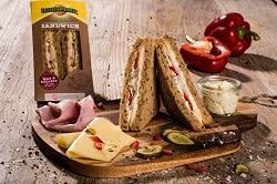 Auf dem Foto ist das Leerdammer Original Sandwich der Sorte Schinken-Käse abgebildet. Im Hintergrund erkennt man das Sandwich noch eingepackt in der Verpackung aus Pappe. Davor im Vordergrund befindet sich ein Schneidebrett. Rechts auf dem Brett sind die beiden Sandwichhälften ausgepackt und aneinandere gestellt worden, sodass man den Belag deutlich erkennen kann. Links vm Sandwich liegen jeweils eine Käsescheibe und eine Schinkenscheibe zur Dekoration.