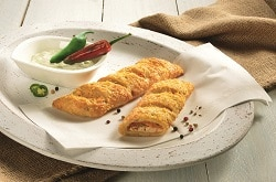 Frischkäse-Pepperoni-Stange, aufgebacken aus dem Tiefkühler, auf einem weißen Teller mit Deko