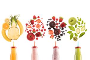 Auf dem Foto sind vier verschiedenen Smoothies zu erkennen. Die Flaschen befinden sich unterhalb des Bildes und sind nur zur Hälfte zu sehen. In den Deckeln stecken Strohlame. Darüber befinden sich Früchte, die den Inhalt der jeweiligen Flasche darstellen.