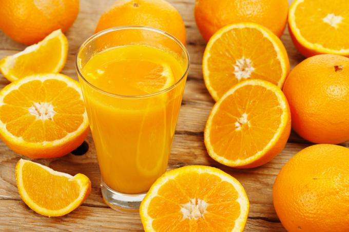 Ein Glas ausgepresster Orangensaft steht in der Mitte von vielen Orangenhälften, aber auch ganzen Orangen auf einem Holztisch.