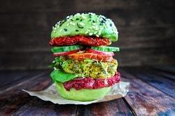 veganer Burger mit grünem Burgerbrötchen und schwarzen Sesam und weißen Sesam. Großer Burger mit getrockneter Tomate und weiterem Gemüse.