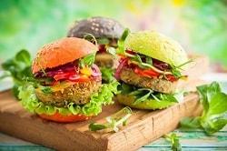 drei vegetarisch-vegane Burger mit viel Salat und farbigen Burgerbrötchen