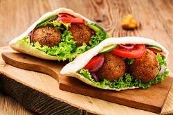 Zwei Falaffel im Brot mit jeweils zwei Falaffelbällchen, Salat, Tomate und Gurke.