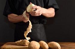 Küchenchef in Betriebskantine oder Gastronomieküche schält Kartoffeln per hand. Er trägt eine schwarze Schurze, ein schwarzes Hemd und steht vor einem schwarzen Hintergrund. Vor ihm liegen vier ungeschälte Kartoffeln. Eine Kartoffel schält er gerade mit einem Messer über dem Holztisch.