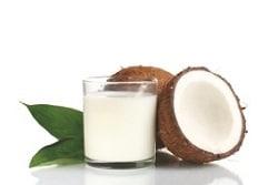 Auf dem Bild ist rechts von einem Glas mit kokosnussmilch geüllt, eine halb aufgeschnittene Kokosnuss zu sehen. Dahinter befindet sich noch eine ganze Kokosnuss. Links vom Glas ist das Bild mit einem grünen Blatt verziert. Der Hintergrund ist weiß.