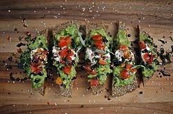 Auf dem Bild ist ein in Scheiben aufgeschnittenes Brot zu sehen. Darauf ist Avocado, etwas Frischkäse und Tomaten zu sehen. Auf dem beschmierten Brot ist das Lüttge Algen-Öl von Evergreen Foods beträufelt.. Das Brot liegt auf einem Holztisch.