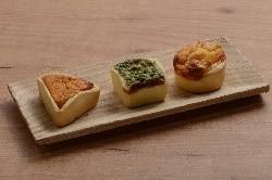Auf dem Foto sind die drei verschiedenen Mini-Quiche-Sorten des Herstellers Maitre Pierre zu erkennen. Sie sind auf einem länglich quadratischem Holzteller auf einem Holzfußboden. Links befindet sich ein dreieckiges Stück, in der Mitte ein quadratisches und rechts eine runde Mini-Quiche.