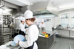 Drei Köche stehen in einer professionellen Gastronomieküche und bereiten sich auf die kommende Arbeit vor. Es scheint eine Betriebskantine oder ähnliches zu sein. Die Küche ist sehr groß und geräumig. Personal befindet sich wenig darin. Die drei Köchinnen tragen weise Jacken, weise Kochmützen und dunkle Schürzen. Auf der Arbeitsplatte befinden sich Produkte, wie Paprika, Aubergine oder Zucchini.