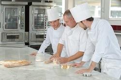 In der Gastronomie bilden die professionellen Köche die Lehrlinge selbst aus. Man sieht einen Koch mit nur zwei jungen Lehrlingen in einer Gastronomieküche stehen und Teig für Brot kneten. Da es nur zwei Auszubildene sind, lässt sich darauf zurückschließen, dass ein Personalmangel in dieser Küche besteht.