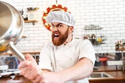 Ein in weiß gekleideter Koch ist frustriert über den Personalmangel in der Gastronomie und hebt eine silberne Pfanne mit beiden Händen hoch um zuzuschlagen. Er hat den Mund weit geöffnet. Im Hintergrund ist eine Küche zu sehen.