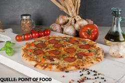Auf dem Bild ist zentral eine große Salamipizza von Point of Food zu sehen. Diese liegt auf einem weißen Holzbrett. Rechts davon erkennt man eine Knoblauchknolle und Ölivenöl, welches in einer Glasflasche ist. Hinter der Pizza ist der restliche Strauch des Knoblauchs und eine große Tomate. Links von der Pizza ist ein kleines Glas mit Gemürzen und davor liegt ein Strauch kleiner Cherrytomaten.