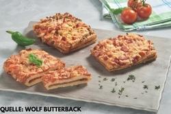 Auf dem Bild sind drei Pizzaschnitten von Wolf Butterback abgebildet. Eine Davon ist aufgeschnitten, sodass erkennbar ist, dass der Teig touriert ist. Als Topping ist die klassische Variante mit Tomatensauce und Käse zu sehen. Die Pizzaschnitten liegen auf einem grauen Holzbrett. Links von der geschnittenen Pizzaschnitte ist eine grüne Pepperoni als Dekoration zu sehen. Im Hintergrund befindet sich ein blau-grün kariertes Handtuch, auf dem Tomaten liegen.