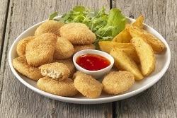 vegetarische NUggets von Quorn sind auf einem weißen Teller abgebildet. Der Hintergrund ist durch die Holzoptik schlicht gehalten. Zu den Nuggets, die sich links auf dem Teller befinden, werden Kartoffelecken und Ketschup serviert. Der Ketschup ist in der Mitte in einer weißen Schale. Zu dekoration befindet sich ein Salatblat unterhalb der Nuggets und Kartoffelecken.
