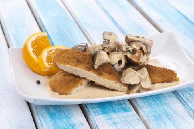 Das vegetarische Schnitzel von Quorn vom Hersteller BestCon ist mit Pilzen und einer Orangen-Pfeffer-Pilz-Soße auf einem weißen quadratischen Teller abgebildet. Es eignet sich super als Fleischalternative. Der Teller steht auf einem blauen Holztisch.