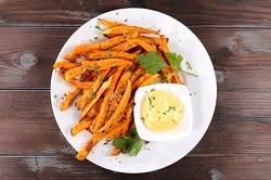 Süßkartoffelpommes befinden sich auf einem weißen Teller, der auf einem dunkelbraunen Holztisch steht. Dazu wird eine Schale Mayonaise gereicht, die sich ebenfalls auf dem Teller befindet.