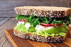 Auf dem Bild ist ein Graubrot zu sehen, welches dick mit Avocadomus, Frischkäse, Radieschen und Salat belegt ist. Die Zutaten befinden sich in dieser Reihenfolge von oben nach unten, bis eine weitere Brotscheibe das Sandwich vollkommen macht. Das Sandwich ist auf einem Holztisch und der Hintergrund ist in einer monotonen Farbe gehalten-.