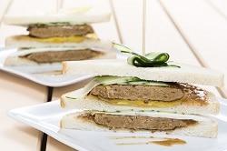 Drei Snadwich Brote mit jeweils drei Scheiben Toast, belegt mit einem Vegetarischen Quorn Burger Pattie, Gurke und einer gelben Snacksoße. Angferichtet auf eienm weißen Teller. Ein Sancwich liegt im Vordergrund, ein zweites etwas verschwommen im Hintergrund