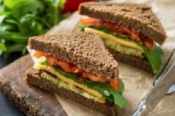 Schwarzbrot ohne Rinde, belegt mit Gouda, Ruccola und Tomaten. Gezeigt im Sandwichschnitt hintereinander.