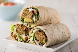 drei Wraps gefüllt mit Falafel und Avocado, mit gemüse, angeschnitten auf einem Teller in Pyramiedenform angerichtet