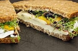Schwarzbrot mit Camembert, honig senf, sprossen, salat und preiselbeeren belegt. gezeigt an der Schnittkante
