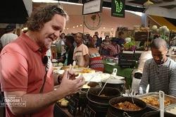 Auf dem Bild ist der Food Experte Andrew Fordyce zu sehen, der auf einem Markt in Südafrika neue Gerichte und Snack testet. Er trägt ein rotes Shirt, einen Sonnenbrille auf dem Kopf und hat eine Tragetasche quer über der Brust. Vor ihm auf dem Tisch sind Kochtöpfe mit Fleisch, aber auch Beilagen wie Reis aufgestellt. Hinter dem Tisch steht ein Verkäufer in einem grau gestreiftem Langarm-Shirt.
