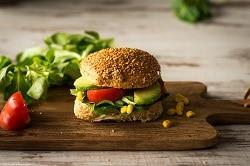 Das Bild zeigt einen Burger auf einer Holzplatte auf einem Holztisch. Der Burger besteht aus einem dunklen Brötchen, Salat, Tomate und Avocadohälften. Im Hintergrund erkennt man Salat, der zur Dekoration dient.